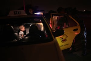 A child cries inside a taxi as a police officer helps migrants to get out of the vehicle on the outskirts of Tumbes.