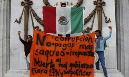 Protesters hold up a Mexican flag