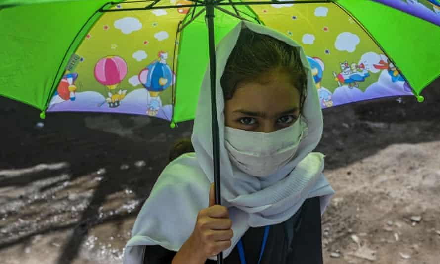 An Afghan school girl holding an umbrella, July 2021.