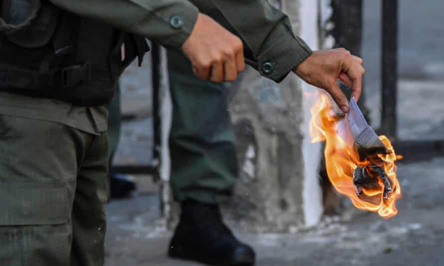 A member of the Bolivarian National Guard burns a copy of amnesty measures for anyone in the military who disavows Maduro