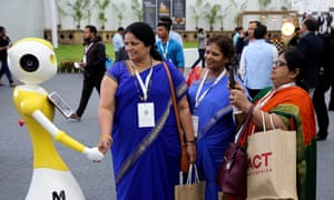 Indian women shake hands with a robot during the Bengaluru Tech Summit 2019 in Bangalore, India