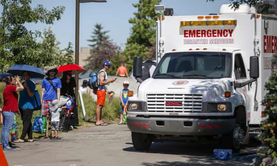 A Salvation Army EMS vehicle is set up as a cooling station as people lineup to get into a splash park while trying to beat the heat in Calgary, Canada