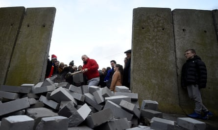 A man uses a sledgehammer to knock down a mock border wall during a protest by anti-Brexit campaigners in Carrickcarnan, Ireland