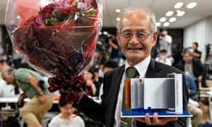 Akira Yoshino holds a model of his developed lithium-ion battery as he celebrates in Tokyo