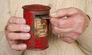 An older woman's hands holding a money tin