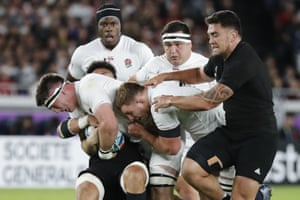 England's Tom Curry, left, is tackled by the New Zealand defence.