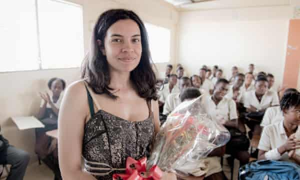 Actor Zuleikha Robinson is presented with flowers on a visit to the Artists for Peace and Justice Academy in Port-Au-Prince.