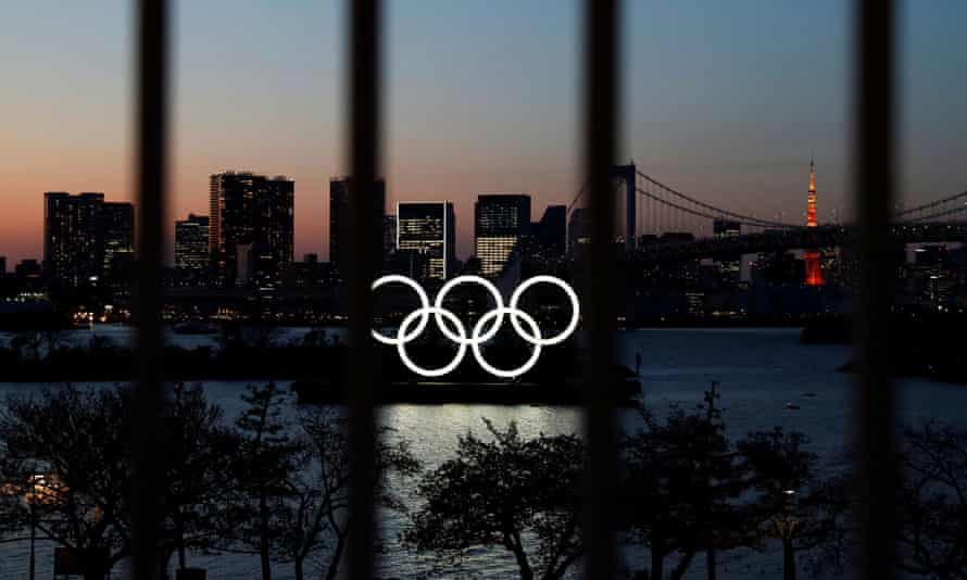 The Olympic rings pictured through a fence in Tokyo.