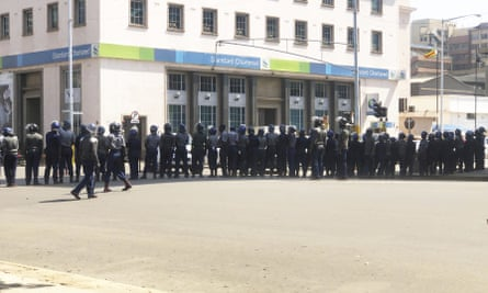Armed riot police block a main road during a patrol on the streets in Harare