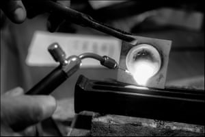 In London Tony Power, of Cox & Power Jewellers heats gold with a blow torch in a crucible until it is molten and can be poured into a trough in the studio behind his shop