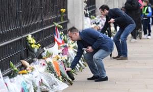 Wellwishers add bunches of flowers outside Buckingham Palace.