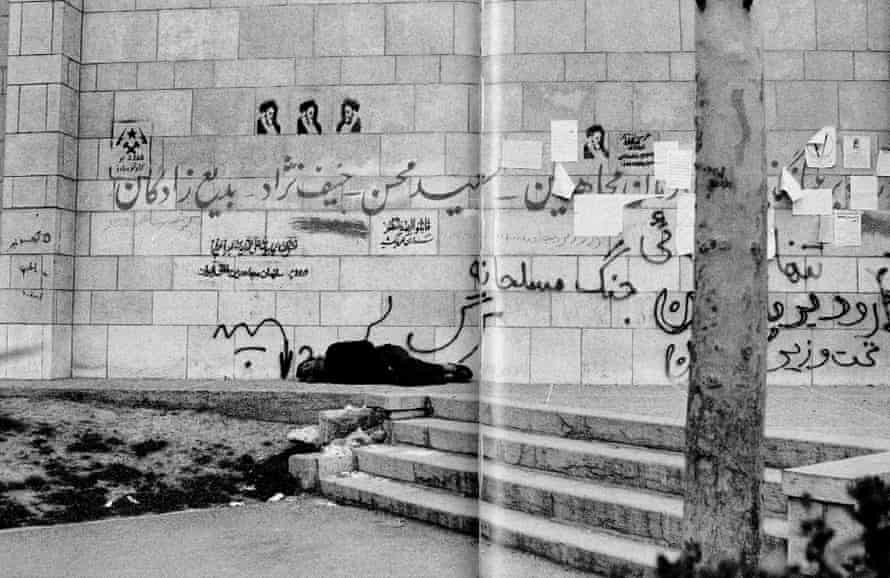 An old man sleeps next to a wall covered with revolutionary graffiti.