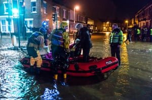 A rescue team helps an elderly woman stranded in the flooded streets after Storm Desmond caused the River Eden to breach its banks in Carlisle