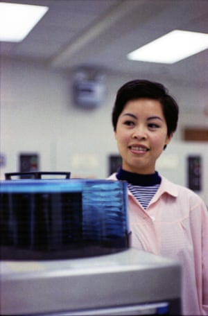 """A computer operator standing next to a disk pack. I'm afraid I can't remember her name."""