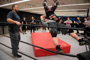Trainer RJ Meyer, a former champion professional wrestler, watches as Scott is thrown from the top rope by one of her male counterparts during a class at the MCW Pro Wrestling training centre in Joppa, Maryland.