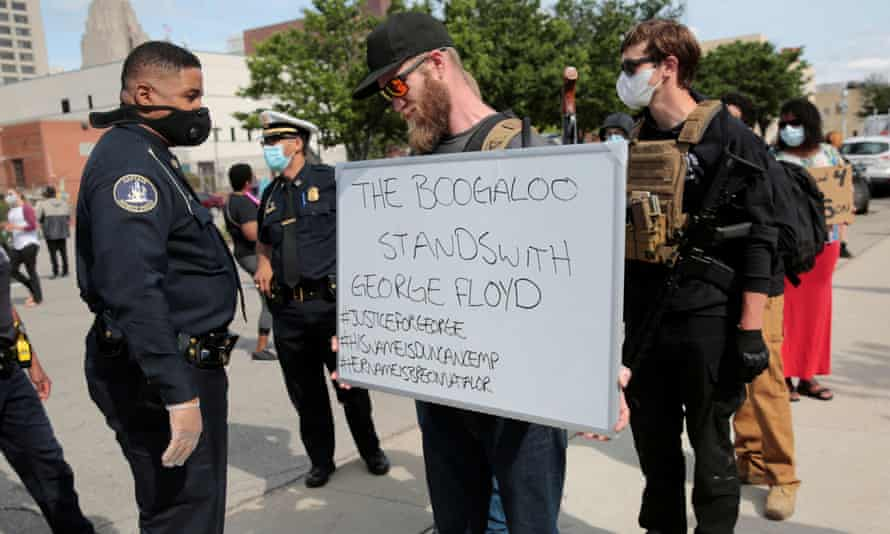 An armed man holds a sign during a rally against the death of George Floyd, in Detroit, Michigan.