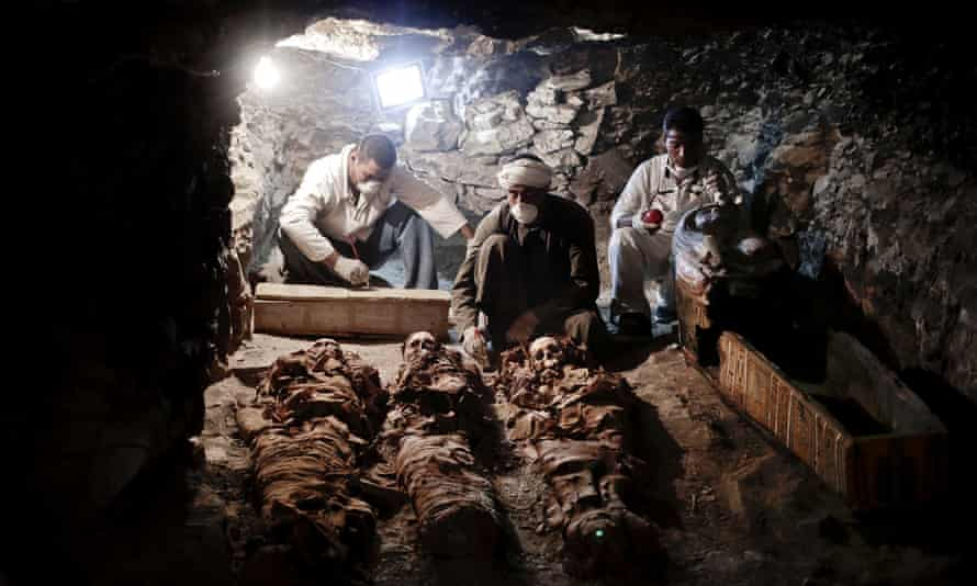 Archaeologists work on mummies found in the New Kingdom tomb in the Valley of the Kings, Egypt