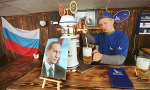 Barman surrounded by pictures of Putin, in the Putin pub in Chelyabinsk