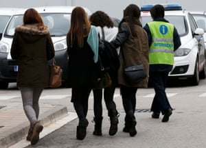 An assistant escorts people in Barcelona believed to be family members of those killed in the Germanwings plane crash