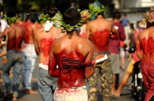 Penitents whip their backs with bamboo during a reenactment of the crucifixion