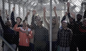 People look out from behind a fence at a detention centre for illegal immigrants in Athens, Greece.