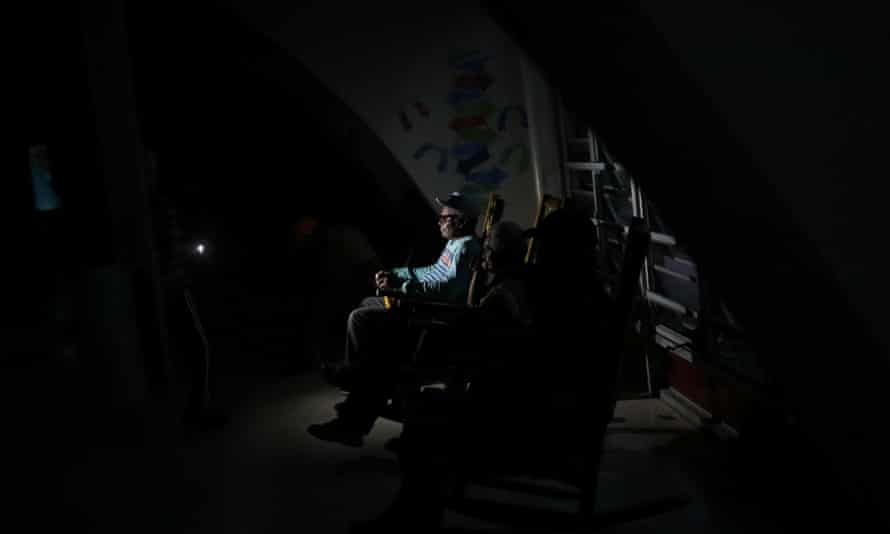 A man uses a flashlight to light up a room at the Las Teresas retirement home, where about 200 elderly people live without electricity following Hurricane Maria.