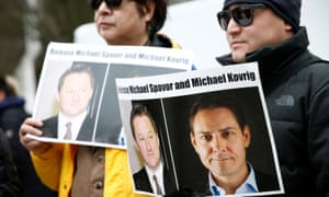 demonstrators holding pictures of Michael Spavor and Michael Kovrig