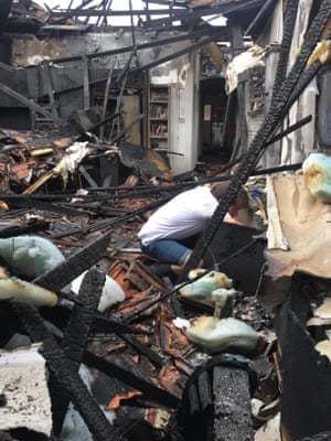 Matt Herbert searches through the remains of his house which burnt down before Christmas.