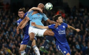 Manchester City's Vincent Kompany is manhandled by Leicester City's Ben Chilwell (left) and Harry Maguire during an extremely tense affair on Monday night. Kompany's howitzer in the second half earned the hosts a dramatic win to put them one victory away from the title.