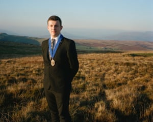 Samuel, from Blaenau Gwent, photographed on a hillside wearing a suit