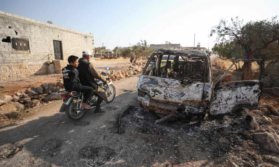 Syrians ride a motorcycle past a burnt vehicle near the northwestern Syrian village of Barisha.