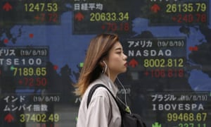 A woman walks by an electronic stock board in Tokyo. Shares rose in expectation of more stimulus, especially from the US Fed and China.