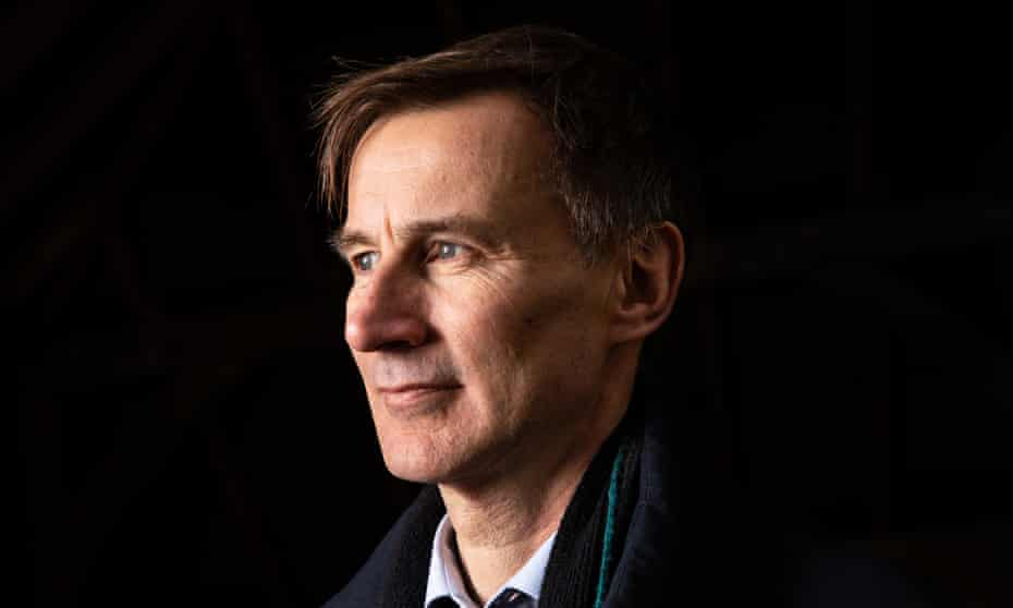 Formal portrait of Jeremy Hunt in open necked shirt,  sweater and coat against a black background