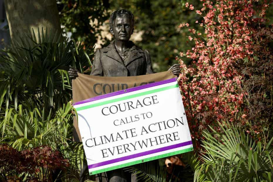 An environmental activist's sign reading 'Courage calls to climate action everywhere' on the statue of Millicent Fawcett in Parliament Square, London.