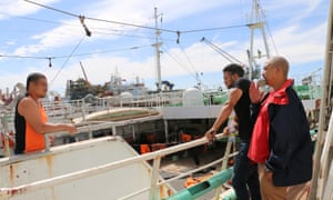 Dane Duplessis (right) and Cassiem Augustus (far right) advise a fisherman in Cape Town's port.