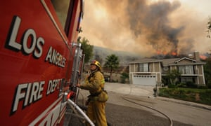 """A firefighter monitors a wildfires in LA. """"I always say, ask a firefighter if climate change is real in Los Angeles,"""" said Eric Garcetti."""