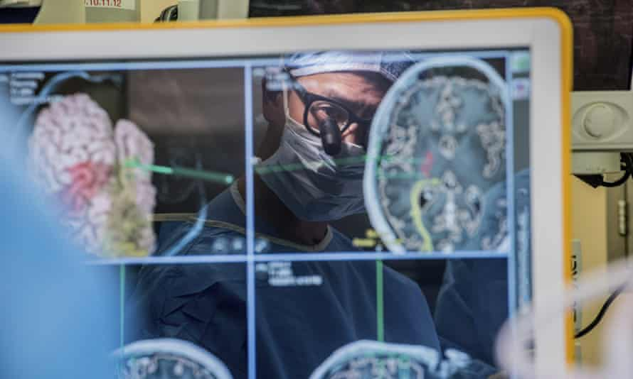 Neurosurgeon Dr Edward Chang's reflection is seen on a computer monitor displaying brain scans in a 2017 photo provided by the University of California.
