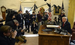 Donald Trump speaks to journalists after signing his tax bill in December. The president's relationship with the press has been increasingly strained.