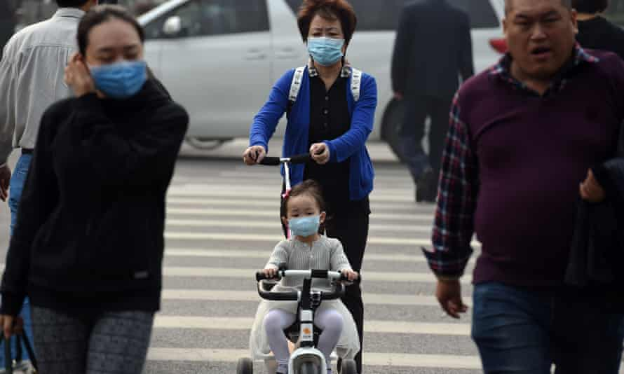 A woman and child wear masks on a polluted day in Beijing, October 2014.