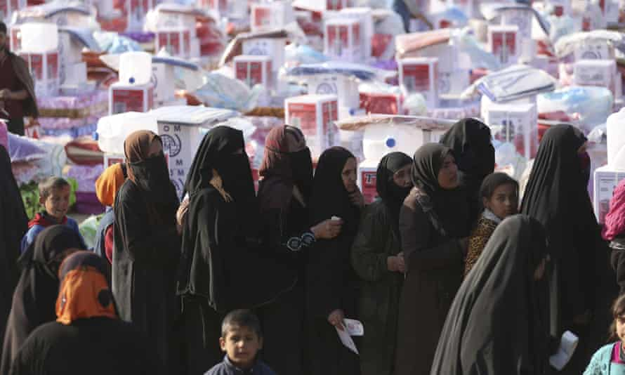 People wait for humanitarian aid to be distributed outside Mosul in northern Iraq.