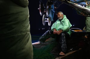 Abu Issam, 63, takes a rest between hauling in fishing nets
