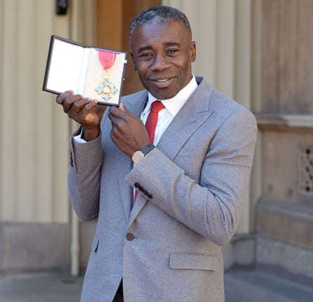 British artist Christopher Ofili holds his award after he was made a CBE for services to art