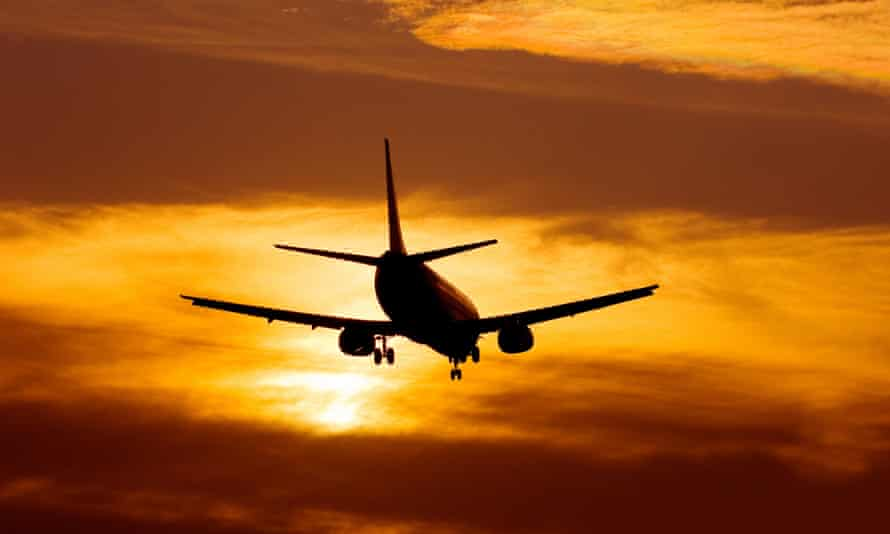 A plane landing at Manchester Airport at sunset.