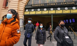 People leave Flinders Street Station on 21 June. Australia updated its Covid face mask position in response to rising coronavirus cases in Melbourne, with new rules making face masks mandatory across Victoria.