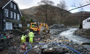 Workmen with diggers clear the beck at Glenridding, Cumbria, after damage wreaked by Storm Desmond.