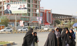 Women walk past posters of Afghan presidential candidates in Kabul.