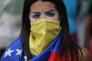 An anti-government protester wears a Venezuelan flag to cover her face