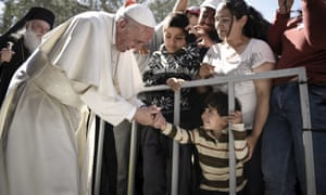 Pope Francis shakes hands with a boy in the Moria refugee camp in Lesbos.