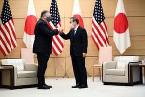 Yoshihide Suga and Mike Pompeo shake hands