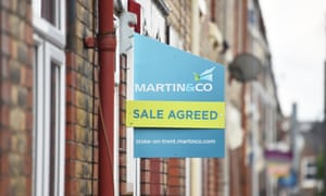 Property signs outside a block of terraced houses advertising homes for sale, let or sold